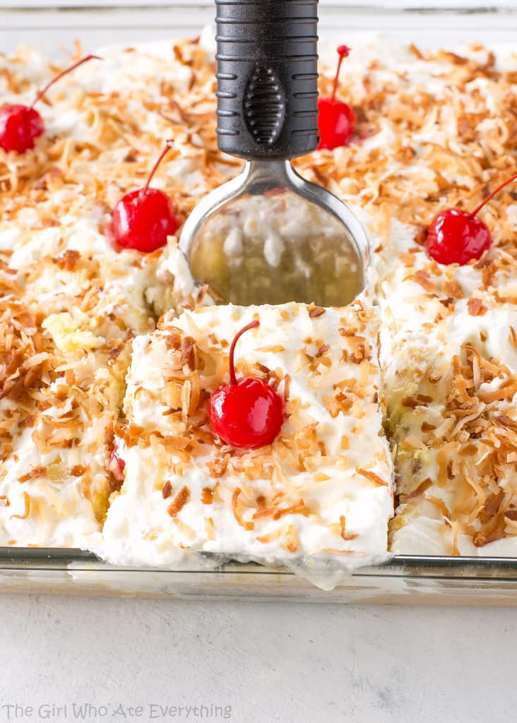 Pina Colada Poke Cake - drizzled with coconut and pineapple and topped with coconut whipped cream and toasted coconut, this cake is the best summer cake out there. the-girl-who-ate-everything.com